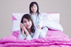 La belle mère joue avec sa fille sur le lit Photographie stock libre de droits