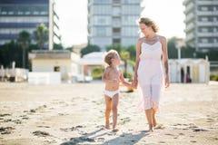 La belle maman de sourire heureuse s'attaque main dans la main avec l'enfant mignon à la plage Images stock