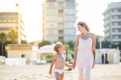 La belle maman heureuse s'attaque main dans la main avec l'enfant mignon à la plage Photo libre de droits