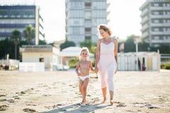 La belle maman heureuse s'attaque main dans la main avec le fils mignon de sourire à la plage de sable Photographie stock