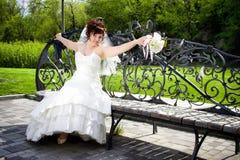 La belle mariée a modifié un banc et un bouquet Photos libres de droits