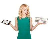La belle, mince blonde compare un comprimé et des livres Images stock