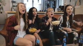 La belle montre TV d'amies, célèbrent le succès Les filles assez émotives de jeunes rient le mouvement lent de observation des sp images libres de droits
