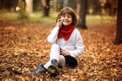 La belle petite fille élégante tenant le téléphone portable et la joie parlent images stock