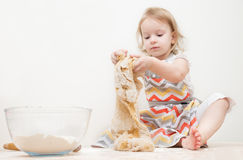 La belle petite fille apprend à faire cuire un repas dans la cuisine Images libres de droits