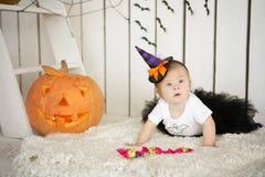 La belle petite fille avec la trisomie 21 se reposant près d'un potiron Halloween s'est habillée comme squelette Image stock