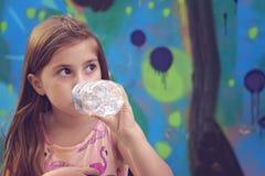 La belle petite fille boit l'eau de la bouteille en plastique images libres de droits