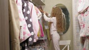 La belle petite fille choisit la robe dans la garde-robe ? la maison Beaut? et mode banque de vidéos