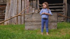 La belle petite fille dans des vêtements bleus nu-pieds se tient dans la cour banque de vidéos