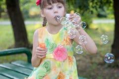La belle petite fille dans la robe de couleur souffle des bulles Image libre de droits