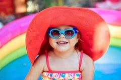 La belle petite fille dans un maillot de bain nage dans t photographie stock libre de droits
