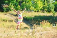 La belle petite fille danse dans le pré au coucher du soleil d'été Image libre de droits