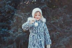 La belle petite fille en bois d'hiver La fille est habillée dans un manteau de fourrure gris Elle tient une boule de Noël blanc photo libre de droits