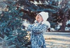 La belle petite fille en bois d'hiver La fille est habillée dans un manteau de fourrure gris Elle tient une boule de Noël blanc photographie stock libre de droits