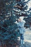 La belle petite fille en bois d'hiver La fille est habillée dans un manteau de fourrure gris Elle tient une boule de Noël blanc image stock