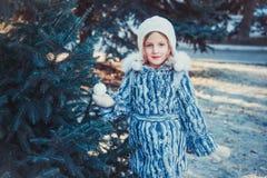 La belle petite fille en bois d'hiver La fille est habillée dans un manteau de fourrure gris Elle tient une boule de Noël blanc photos stock
