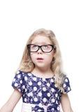 La belle petite fille en verres a étonné la recherche sur le somethi Photos stock