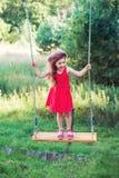 La belle petite fille est sianding et souriante sur l'oscillation au summe Photos libres de droits