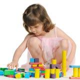 La belle petite fille joue les cubes en bois en couleur Images stock
