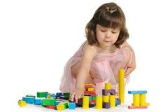 La belle petite fille joue les cubes en bois en couleur Image stock