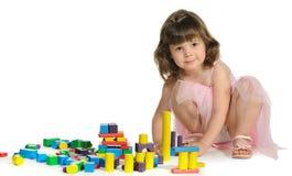 La belle petite fille joue les cubes en bois en couleur Images libres de droits