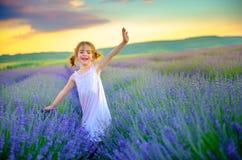 La belle petite fille marche et a l'amusement sur le gisement de lavande photo stock