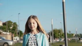 La belle petite fille marche et tourne autour à la caméra au quai ensoleillé banque de vidéos