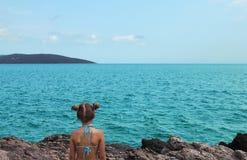 La belle petite fille s'assied sur la plage rocheuse Photo stock