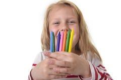 La belle petite fille tenant les crayons multicolores a placé dans le concept d'éducation d'écoliers d'art Photographie stock