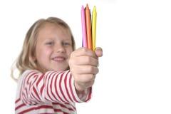 La belle petite fille tenant les crayons multicolores a placé dans le concept d'éducation d'écoliers d'art Photos stock