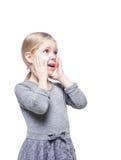 La belle petite fille a étonné la recherche sur quelque chose d'isolement Images stock