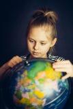 La belle petite fille tournoie le globe Image stock