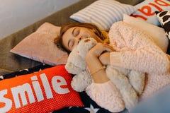 La belle photo de l'adolescent blond mignon étreignant l'ours de nounours tout en se trouvant sur les oreillers Photo libre de droits