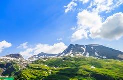 La belle photo du paysage alpin avec la neige et me verdissent Photos stock