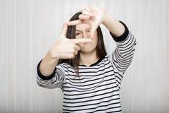 La belle photographe de fille regarde par un cadre fait de doigt Photos stock