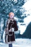 la belle position de jeune femme regarde le chapeau brun loin de port de béret de manteau dans la forêt scandinave neigeuse froid Photo libre de droits