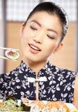 la belle profondeur mangeant des yeux mettent en place les jeunes peu profonds de femme de sushi d'orientation Photos stock
