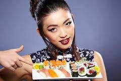 la belle profondeur mangeant des yeux mettent en place les jeunes peu profonds de femme de sushi d'orientation Photographie stock libre de droits