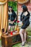La belle rétro femme regarde dans le miroir image stock