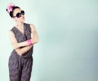 La belle rétro fille dans des lunettes de soleil avec un arc sur sa tête est dans le studio sur un fond bleu Images libres de droits