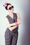La belle rétro fille dans des lunettes de soleil avec un arc sur sa tête est dans le studio sur un fond bleu Photo libre de droits