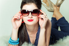 La belle rétro fille dans des lunettes de soleil avec un arc sur sa tête est dans le studio sur un fond bleu Photos libres de droits