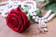 La belle rose de rouge avec la perle perle sur un fond beige Photographie stock