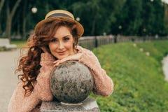 La belle, rousse fille dans le chapeau de vintage se penche ses coudes sur une boule de granit en parc, souriant à l'appareil-pho photos libres de droits
