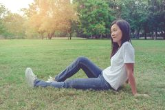 La belle séance asiatique de femme et le mensonge détendent sur le champ de pré d'herbe verte en parc Elle bonheur et rafraîchiss photos libres de droits
