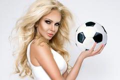 La belle, sexy femme blonde s'est habillée dans l'habillement de sports, jeu dans le football Image stock