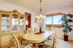 La belle table de salle à manger en bois découpée a placé dans la chambre lumineuse photographie stock libre de droits