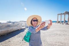 La belle voyageuse mûre de femme prend des photos au téléphone portable Photos stock