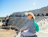 La belle voyageuse mûre de femme, s'assied sur les étapes de l'amphit Images stock