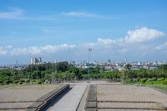 La belle vue de la place à la grande ville avec un ciel bleu et des nuages blancs, au milieu sur le mât un drapeau se développe Images stock